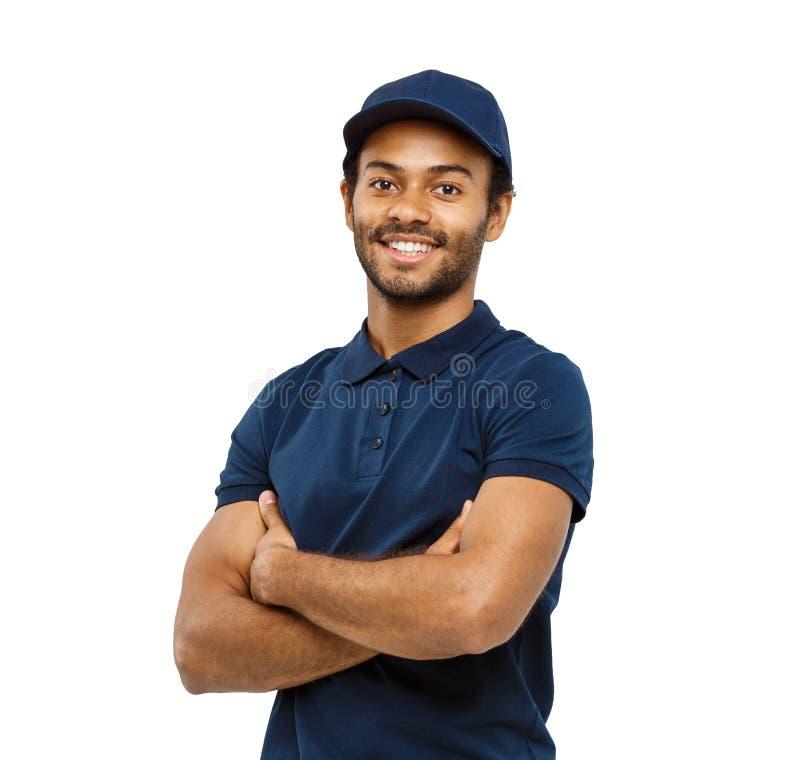 Концепция поставки - красивый Афро-американский работник доставляющий покупки на дом пересек оружия сверх изолированный на белой  стоковое изображение rf