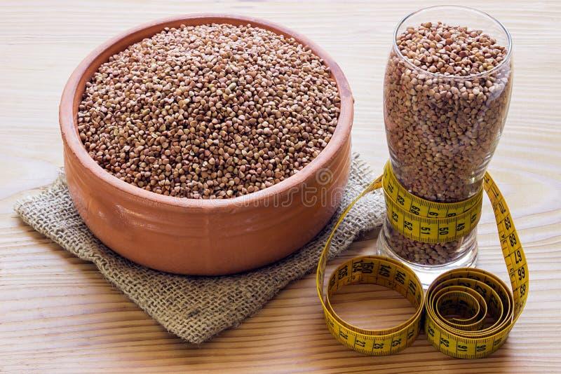 Концепция - потеря веса Гречиха в керамическом баке, измеряя кран стоковое изображение