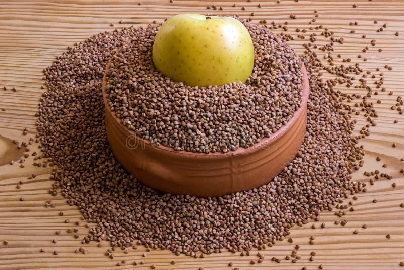 Концепция - потеря веса Гречиха в керамическом блюде и яблоке стоковые фото