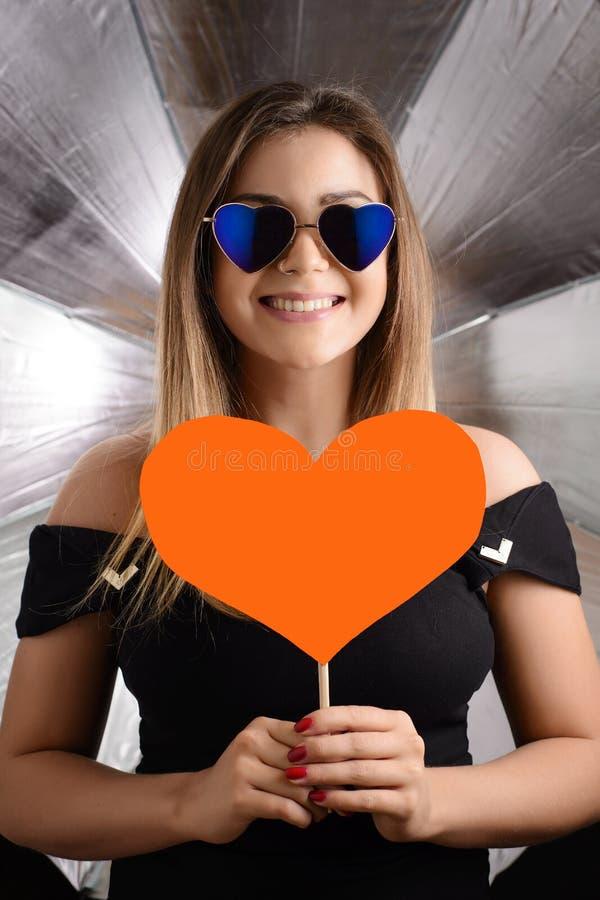 Концепция подарка дня ` s валентинки Красивая женщина держа знак влюбленности стоковая фотография rf