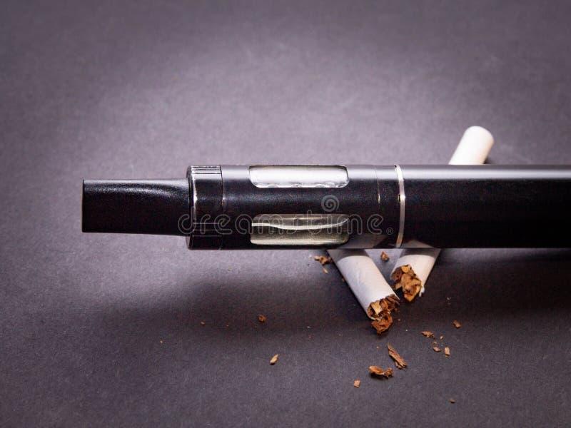 Концепция по борьбе с курением вапоризатора на изоляте сигареты на темной предпосылке стоковые изображения rf
