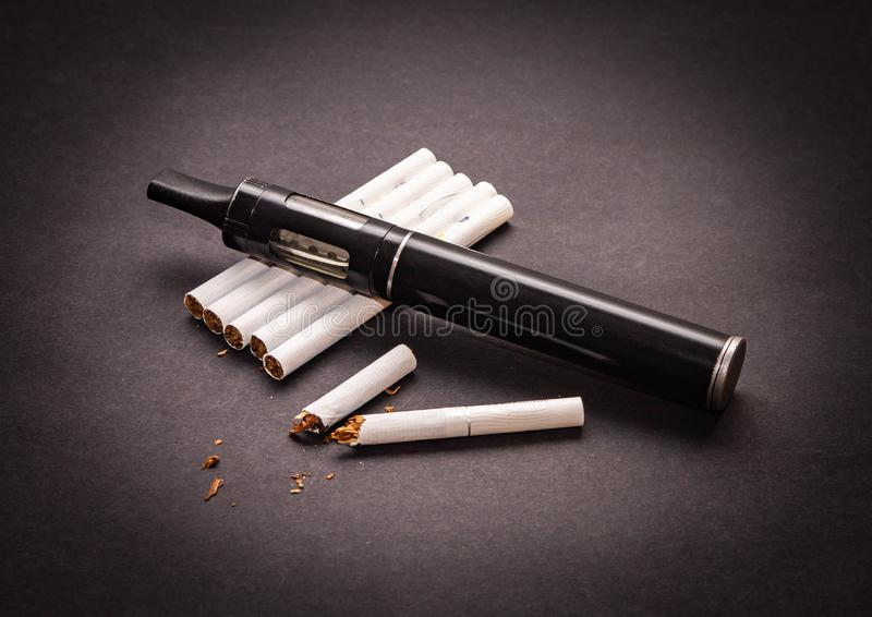 Концепция по борьбе с курением вапоризатора на изоляте сигареты на темной предпосылке стоковые изображения