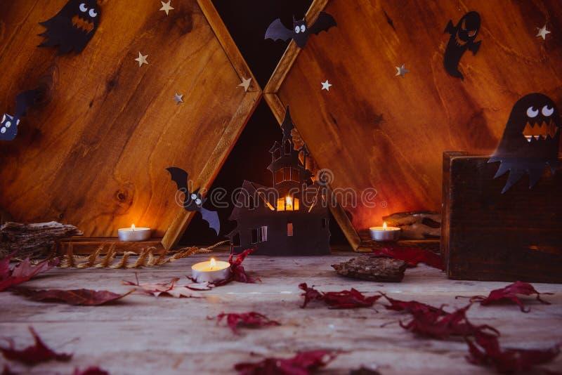 Концепция праздника хеллоуина Освещать бумажные силуэты старого замка, призраки, ведьма, летучие мыши, свечи на деревянной предпо стоковые изображения rf