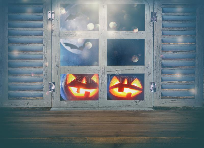 Концепция праздника хеллоуина Пустая деревенская таблица перед преследовать предпосылкой ночного неба и старым окном Подготавлива стоковые изображения