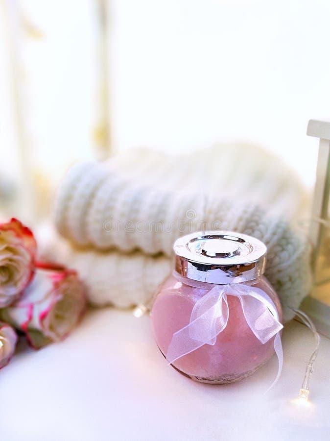 Концепция праздника Hygge Косметический опарник, связанный свитер, розы на белой предпосылке стоковые фотографии rf