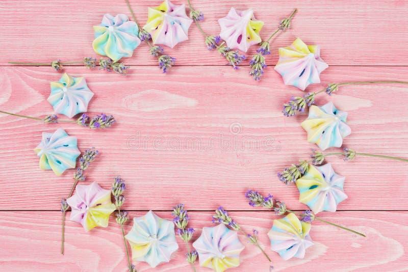 Концепция праздничной предпосылки, на розовых деревянных досках выровнянных с красочными меренгами и голубыми цветками, космос эк стоковые изображения