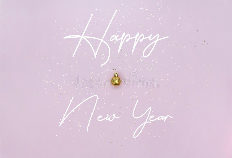 Концепция празднования Нового года Золотой рождественский шар, летучий и золотой звездочки сияет на пастельно-розовом фоне стоковая фотография