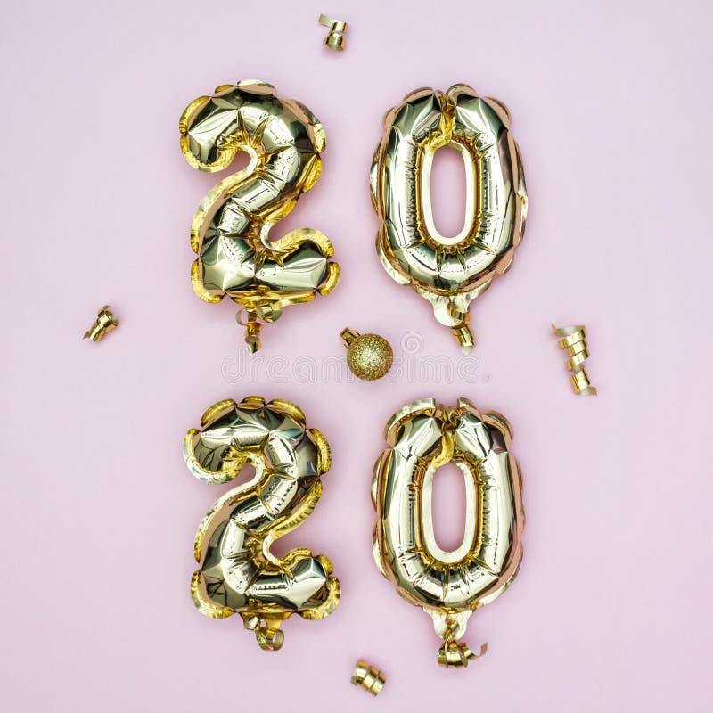 Концепция празднования Нового 2020 года Золотые фольги нумерики 2020 года и золотые звезды на пастельном розовом фоне Вечеринка в стоковые фото