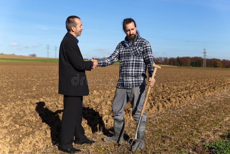 Концепция: Приземлитесь хватать с бизнесменом и фермером стоковое фото