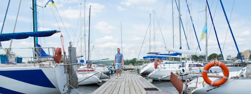 Концепция приключения путешествием каникул летнего времени Красивый человек тратя свободное время идя на Марине стоковое фото