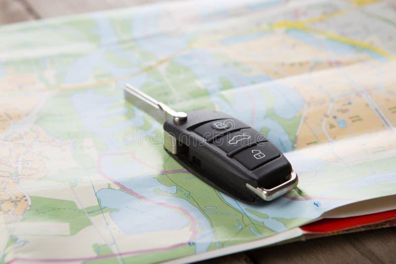 Концепция проката автомобилей - ключ автомобиля на карте стоковое фото