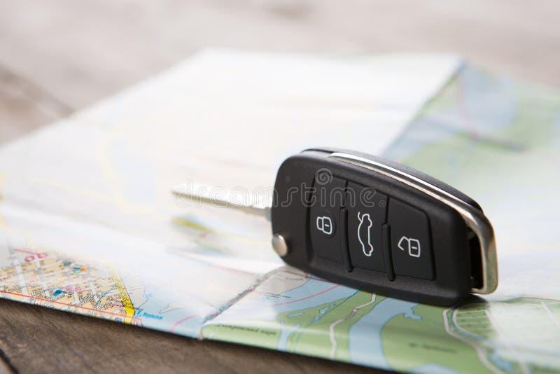 Концепция проката автомобилей - ключ автомобиля на карте стоковая фотография rf