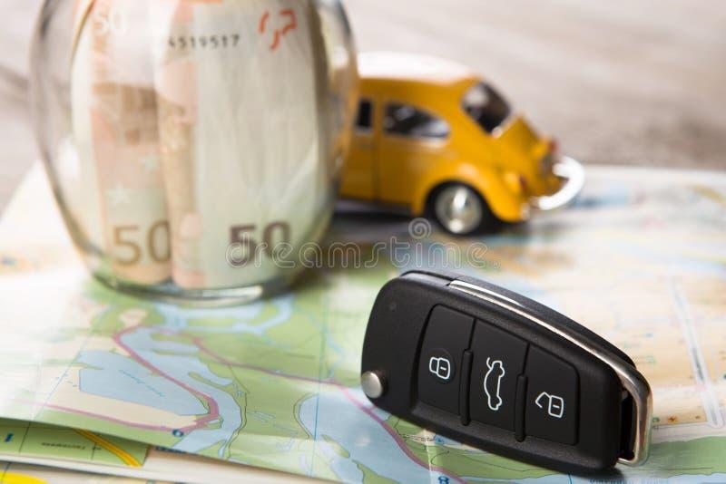 Концепция проката автомобилей - ключ и деньги автомобиля на карте стоковая фотография rf