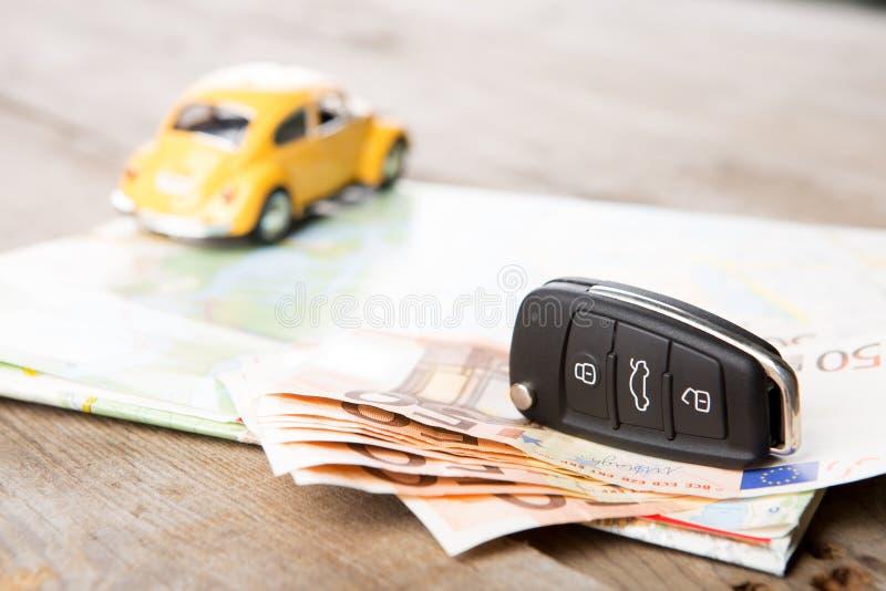 Концепция проката автомобилей - ключ и деньги автомобиля на карте стоковое фото