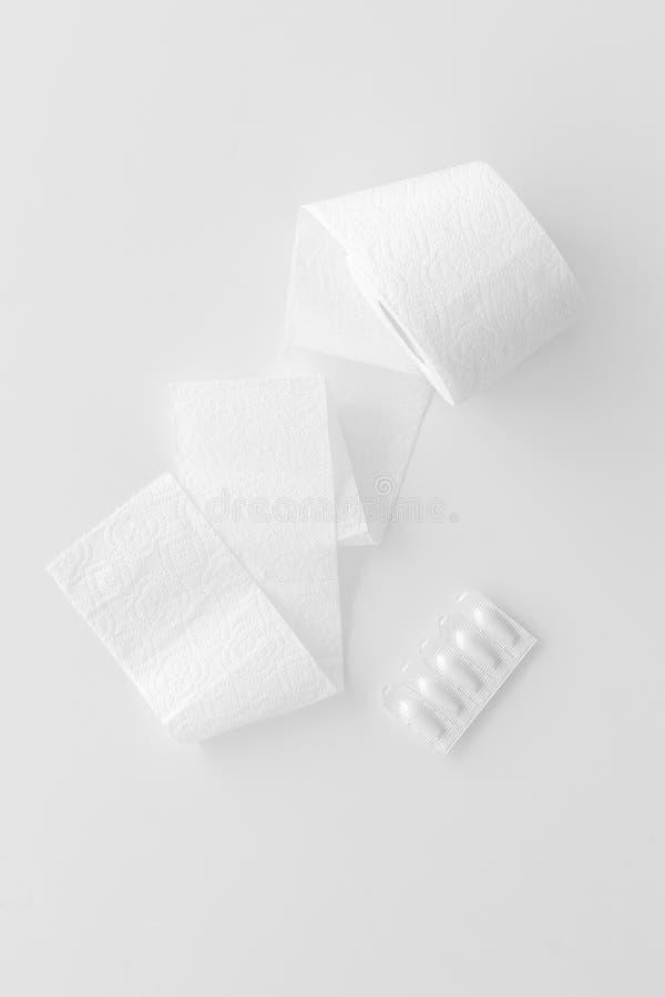 Концепция проктологии с креном туалетной бумаги и ректальным суппозиторием на белом взгляде сверху предпосылки стоковое фото rf