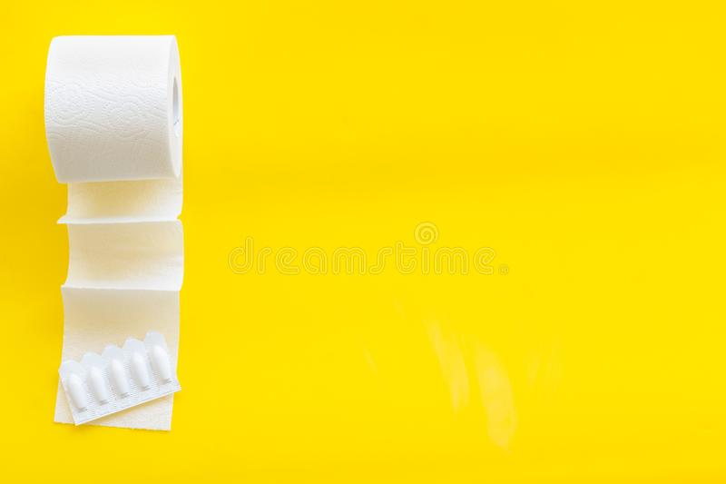 Концепция проктологии с креном туалетной бумаги и ректальным суппозиторием на желтом космосе взгляда сверху предпосылки для текст стоковое изображение rf