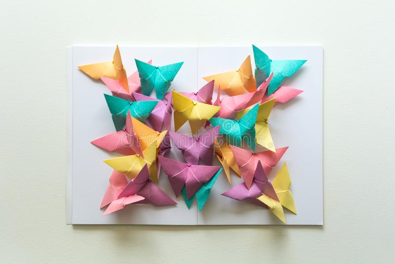 Концепция психических здоровий Красочные бумажные бабочки сидя на книге в форме бабочки Эмоция сработанности Origami стиль отрезк стоковая фотография rf