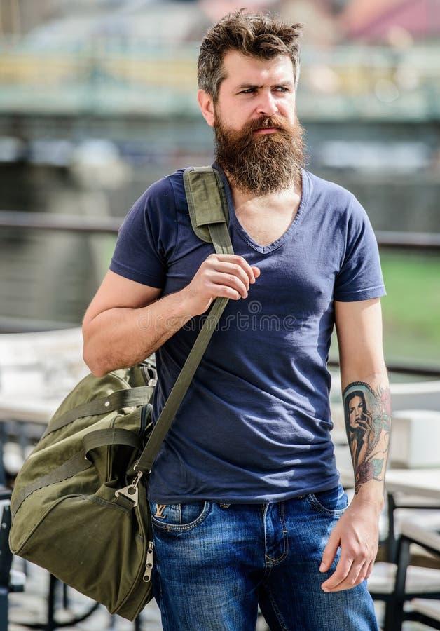 Концепция путешествовать и каникул Мышечный человек с бородой и усик нося большую sporty сумку Турист исследует город стоковые фотографии rf