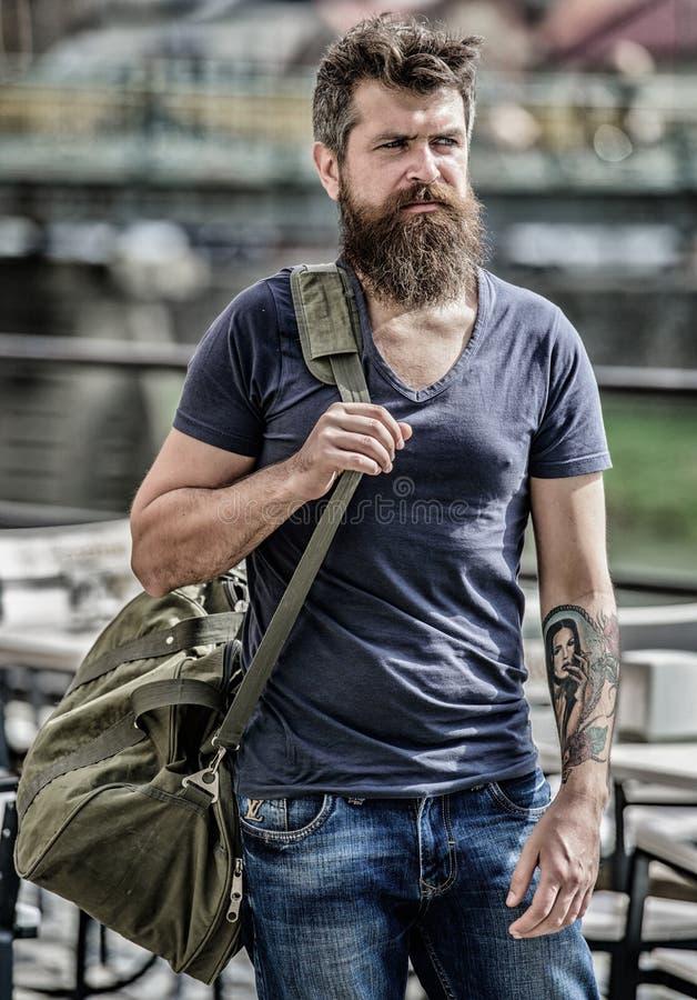Концепция путешествовать и каникул Мышечный человек с бородой и усик нося большую sporty сумку Турист исследует город стоковое изображение rf