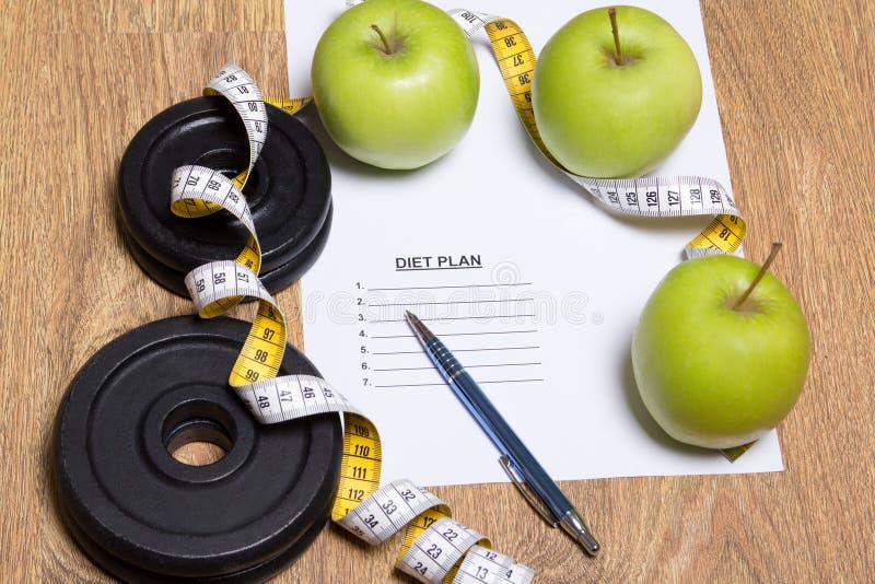 Концепция плана диеты - яблоки, лента измерения и гантель стоковое изображение rf