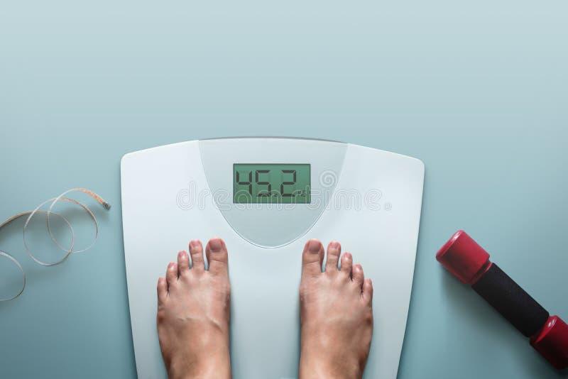 Концепция работать и диеты, женщина стоя на Sc веса цифров стоковое фото