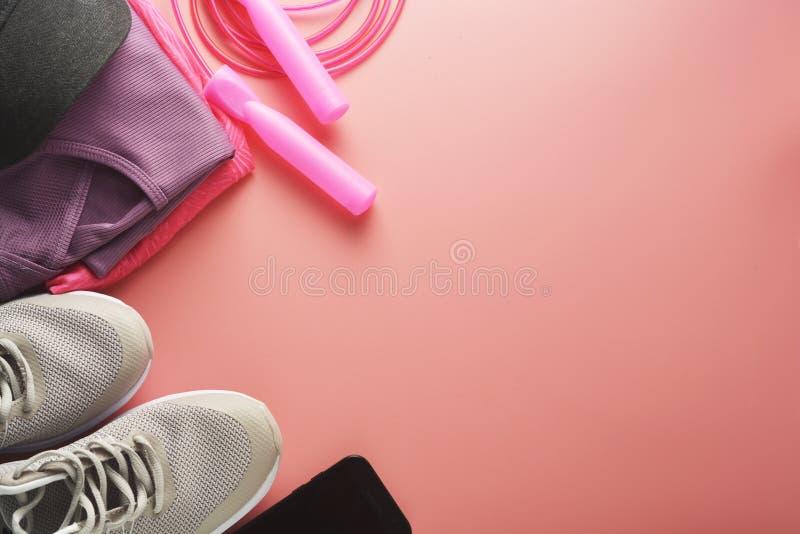 Концепция разминки, квартира кладет с космосом экземпляра Ботинки спорта, скача веревочка, одежды йоги над розовой предпосылкой З стоковые изображения