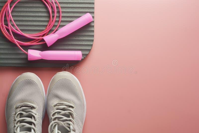 Концепция разминки, квартира кладет с космосом экземпляра Ботинки спорта, скача веревочка, одежды йоги над розовой предпосылкой З стоковая фотография rf