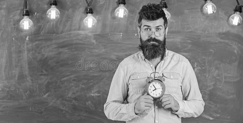 Концепция расписания школы Человек с бородой и усик на спокойной стойке стороны в классе Бородатый хипстер держит часы стоковое фото rf