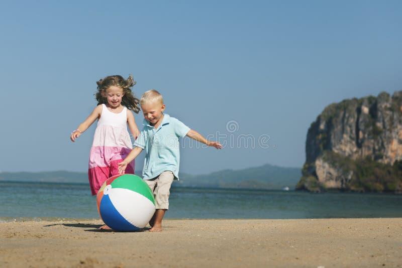 Концепция ребенка сестры брата отпрыска пляжа шарика детей стоковое фото