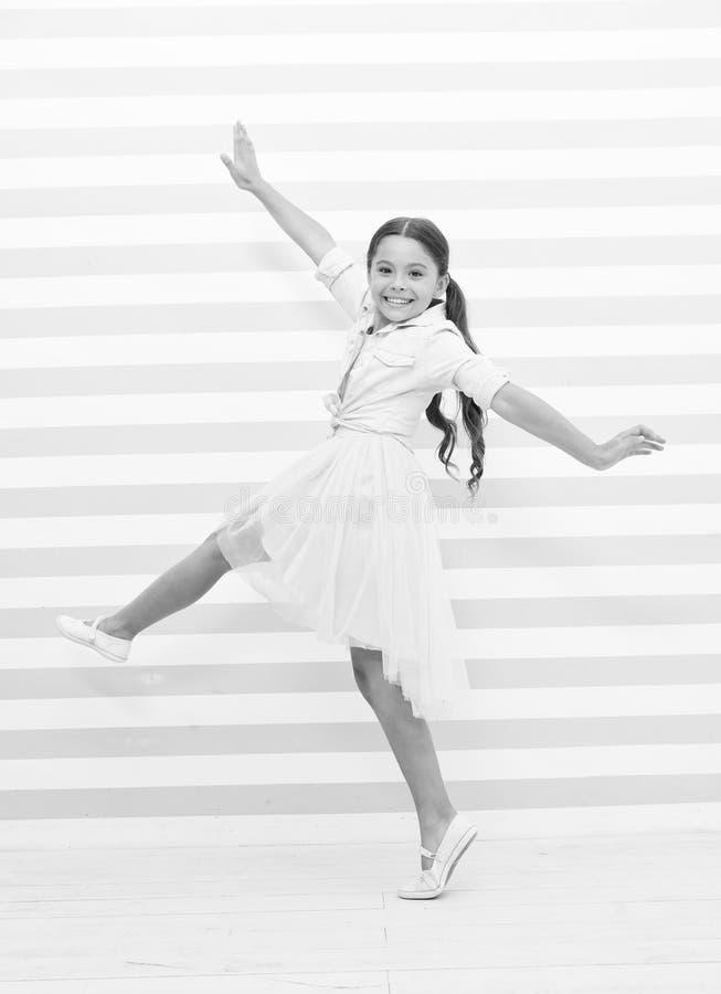 Концепция ребенка Счастливые танцы маленького ребенка Улыбка девушки ребенка в платье моды Ребенок и детство Чувство свободы стоковые фото