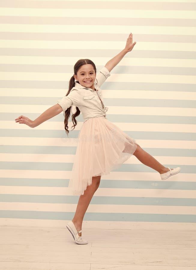 Концепция ребенка Счастливые танцы маленького ребенка Улыбка девушки ребенка в платье моды Ребенок и детство чувство свободы стоковое фото rf