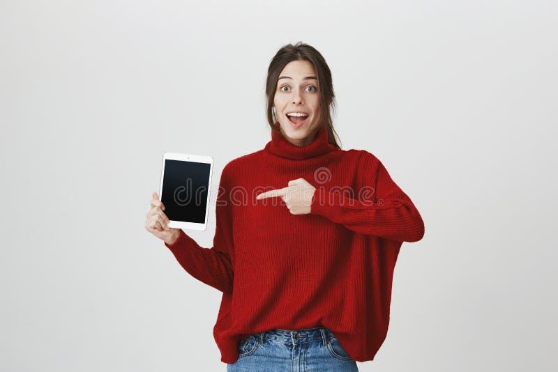 Концепция рекламы и эмоций Ультрамодная тонкая девушка с длинными коричневыми волосами при изумленное выражение, держа таблетку и стоковые фотографии rf