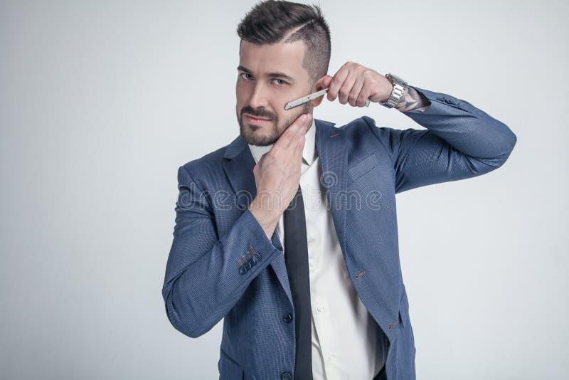 Концепция рекламы парикмахерскаи Бизнесмен с серьезной стороной изолированной на белой предпосылке Человек с бородой держит бритв стоковые фото
