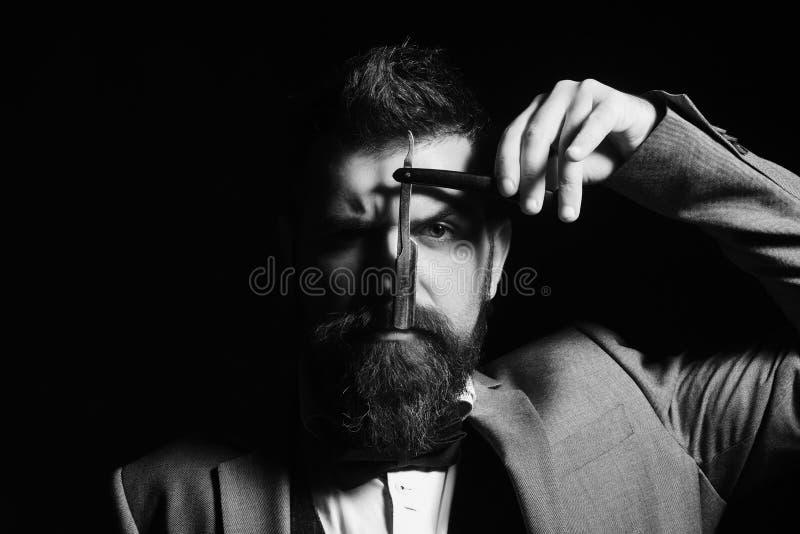Концепция рекламы парикмахерскаи Мачо в официально костюме бреет бороду стоковая фотография