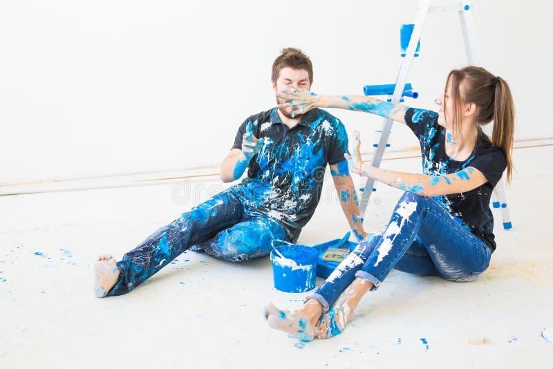 Концепция реновации, redecoration и людей - молодая пара делая реновацию в новом доме и иметь потеху на перерыве стоковое фото