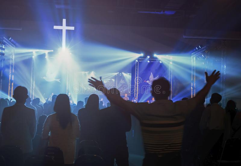Концепция рождества: Запачканный христианский бог поклонению конгрегации совместно в зале церков перед этапом музыки и световом э стоковое изображение