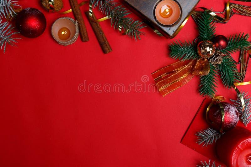 Концепция рождества, правильная позиция положенная, свечи, циннамон, игрушки, спрус, космос для текста, на красную предпосылку стоковое фото