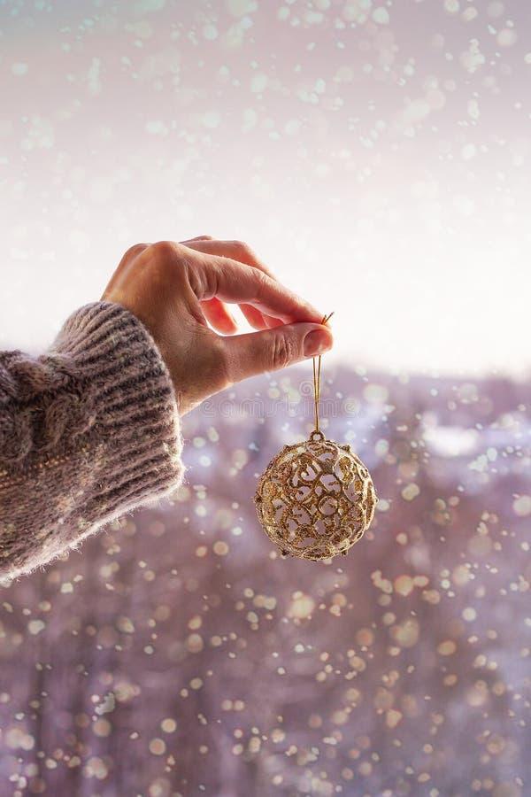 Концепция рождества с рукой и золотым шариком - игрушкой рождественской елки Украшение рождества на предпосылке снега стоковое фото