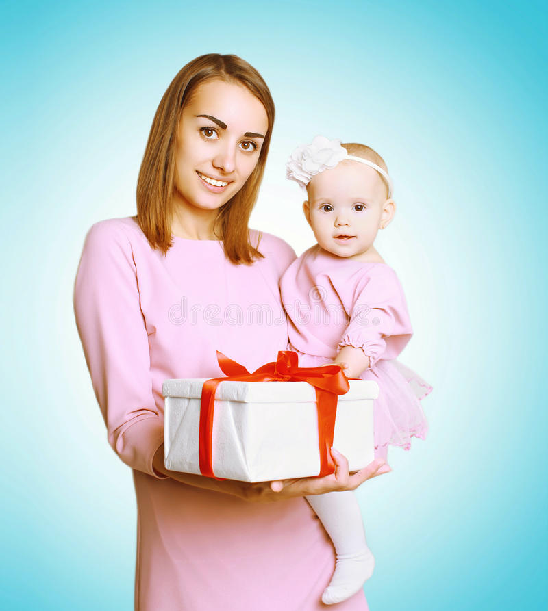 Концепция рождества - счастливые усмехаясь мать и младенец в розовом платье с подарком коробки стоковая фотография rf