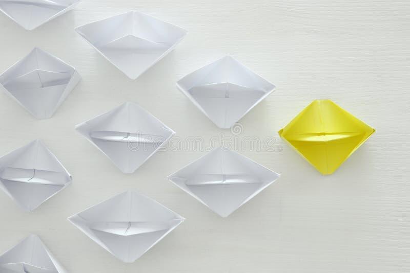 концепция руководства, следующие желтой бумажной шлюпки ведущие над белой предпосылкой стоковая фотография