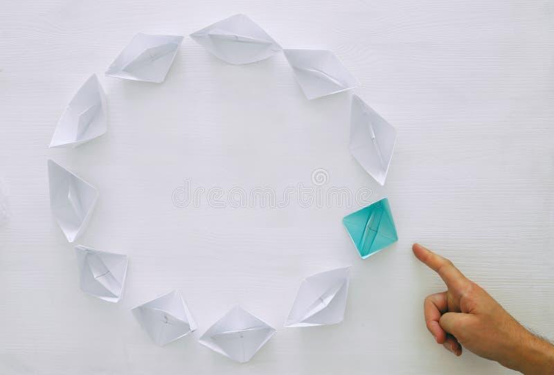 концепция руководства, следующие шлюпки голубой бумаги ведущие над белой предпосылкой стоковое изображение