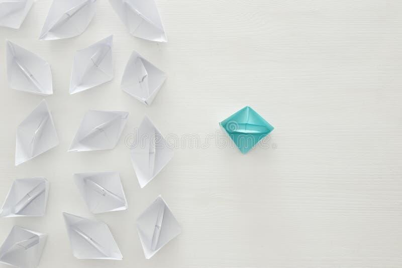 концепция руководства, следующие шлюпки голубой бумаги ведущие над белой предпосылкой стоковое изображение rf