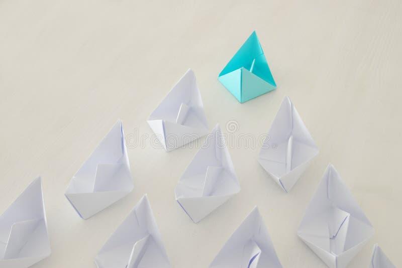 концепция руководства, следующие шлюпки голубой бумаги ведущие стоковое изображение