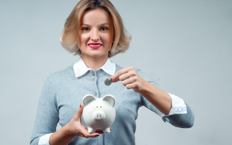 Концепция сбережений банк держа piggy женщину стоковые изображения rf