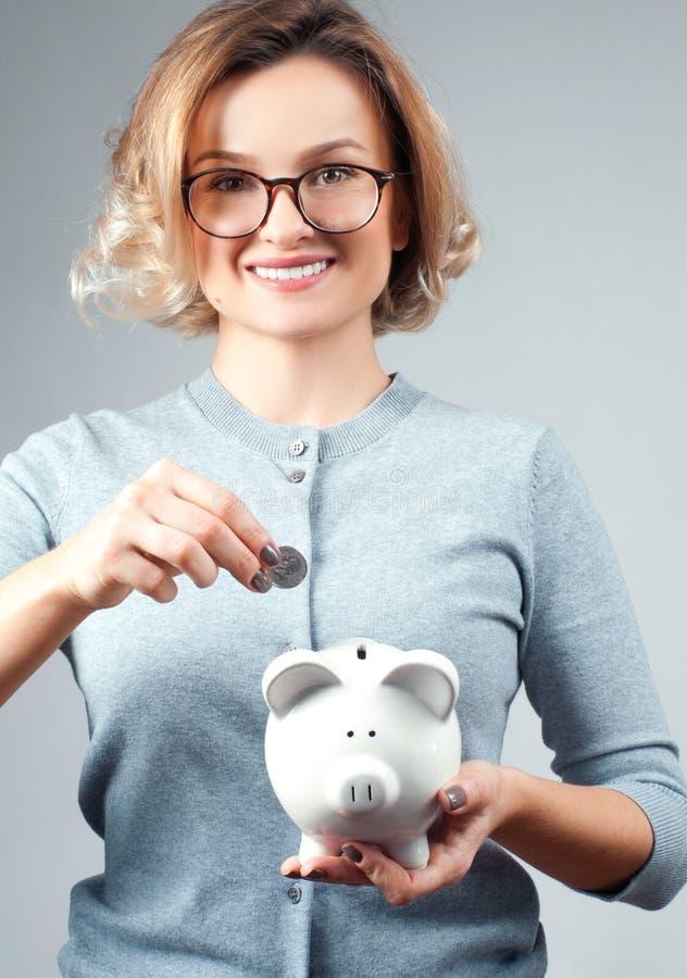 Концепция сбережений банк держа piggy женщину стоковая фотография