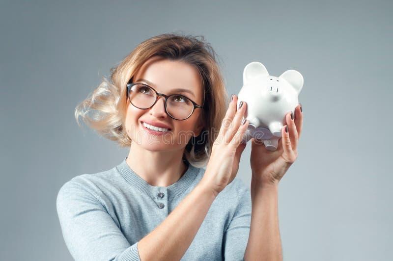 Концепция сбережений банк держа piggy женщину стоковое фото