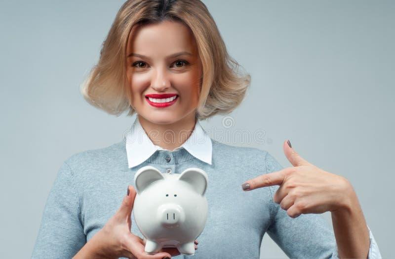 Концепция сбережений банк держа piggy женщину стоковое изображение