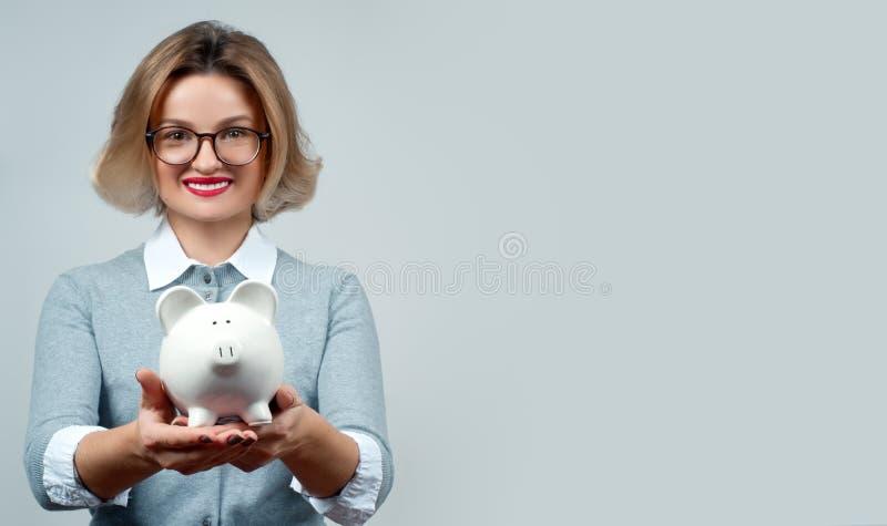 Концепция сбережений банк держа piggy женщину стоковое изображение rf