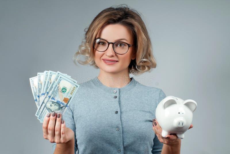Концепция сбережений Женщина держа копилку и пук банкнот денег стоковое изображение rf