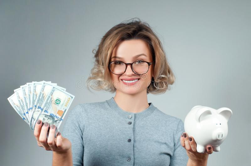 Концепция сбережений Женщина держа копилку и пук банкнот денег стоковая фотография rf